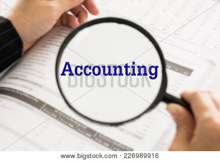 Accounting Concept.  Accountant Using Magnifier Glass Accounting Word From Data In Balance Sheet.