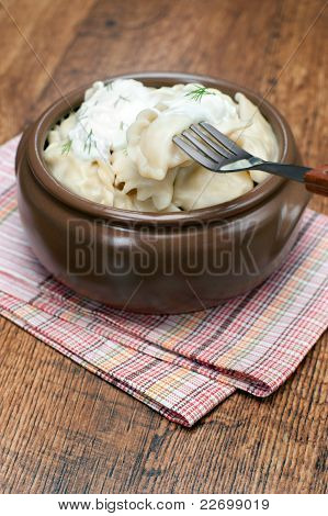Pelmeni with sour cream and dill