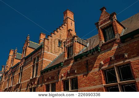 Brick Houses, Roofs And Chimneys Contrasting With Blue Sky In Bruges. With Many Canals And Old Build