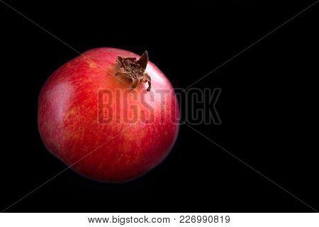 Fresh Red Garnet Lies On A Black Background. Fruit. Concept-healthy Food, Raw Food, Vegetarianism, F