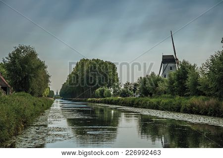 Old Windmill Next To Canal With Bushes And Grove Alongside, In The Late Afternoon And Blue Sky, Near
