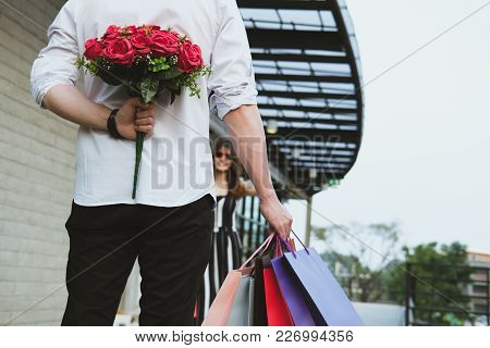 Man Holding Shopping Bag & Bouquet Of Red Roses Behind His Back For Woman. Boyfriend Surprise Girlfr