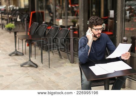 Businessman Arguing, Discussing Project With Partner By Smartphone And Reading Papers At Cafe Table.