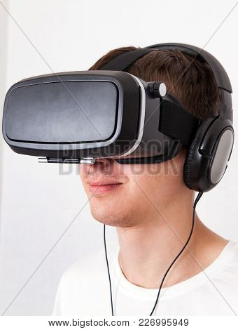 Young Man In Virtual Reality Glasses By The White Wall