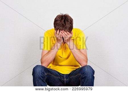 Sad Young Man In The Room On The White Wall Background