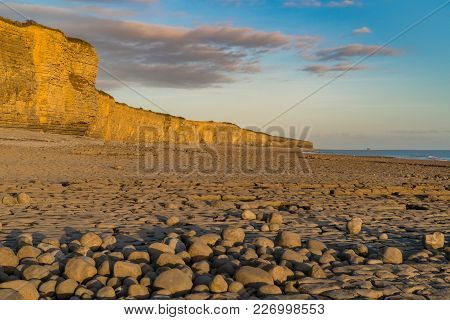 The Stones And Cliffs Of Llantwit Major Beach In The Evening Sun With Some Clouds Over The Cliffs, S