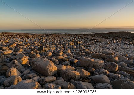 The Stones Of Llantwit Major Beach With The Bristol Channel In The Evening Light, South Glamorgan, W