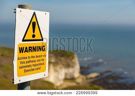 Warning Sign With Blurry Flamborough Head Coast And Cliffs In The Background, Near Bridlington, East