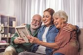Portrait of laughing grandparents and smiling young woman looking at photo in room. Remembrance concept poster
