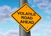 Volatility in the stock market symbol represented by a yellow road warning sign showing the hazards of a volatile trading sesion at the dow jones or wall street in which equities go up and down in a dramatic way. poster