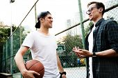 Young adult male friends playing basketball in the park poster