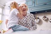 Our little secret. Pleasant charming elderly woman hugging her little granddaughter and listening to her secret while the girl sitting on the kitchen counter and whispering into her ear poster