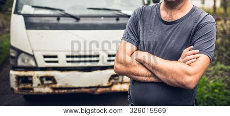 Male Driver In Old-fashioned T-shirt Has Crossed Hands And Stays Near His Old Rusty Truck On The Par