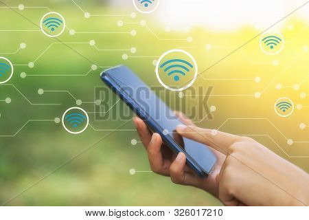 Woman Hand Using Smart Phone At Outdoor Nature Park And Sunset Sky With Wifi Icon Line Abstract Back