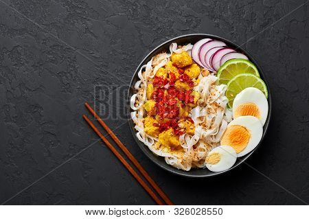 Nan Gyi Thoke In Black Bowl At Dark Slate Background. Nan Gyi Thohk Is Popular Burmese Cuisine Dish