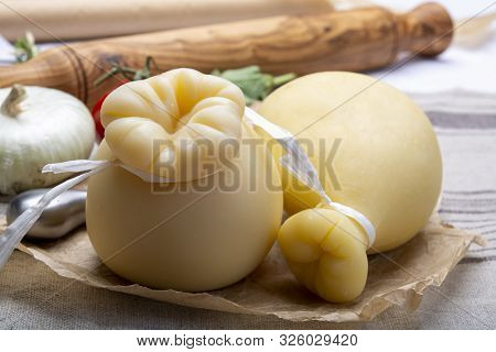 Italian Provolone Or Provola Caciocavallo Hard Cheeses In Teardrop Form Served On Old Paper Close Up