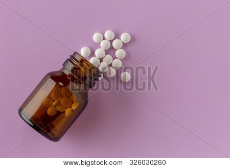 White Round Tablets Scattered Around A Glass Bottle Of Medicine