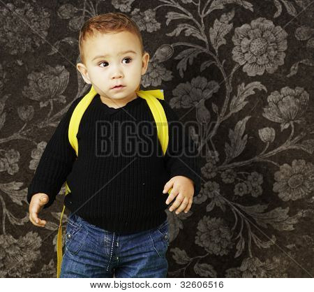 portrait of an adorable kid carrying a yellow backpack against a vintage background