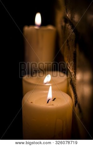Background Or Texture Of Large White Burning Candles In Dark Room Near Brick Wall. Holiday. Hellowee