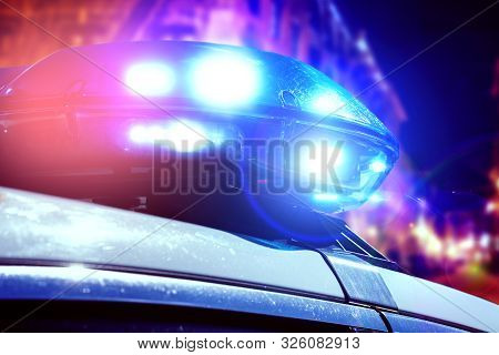 Blue And Red Light Flasher Of A Patrol Police Car At Night. Police Force Department In Full Activity