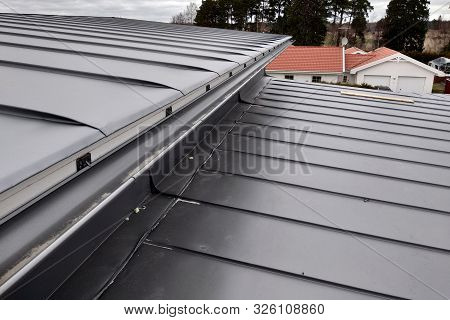 Close-up Detail Of House Roof Made From Gray Metal Sheets.