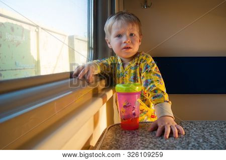 A Bright Cute Three-year-old Boy In Yellow Pajamas Rides On A Train By The Window, Behind Which A Du