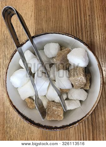 Top View Of A Bowl With Pieces Of White And Brown Sugar Cubes And With Sugar-tongs On A Wooden Table