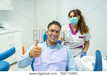 Male Patient At The Dentist Dentist Smiling To The Camera .dentist Doing An Examination To A Male Pa