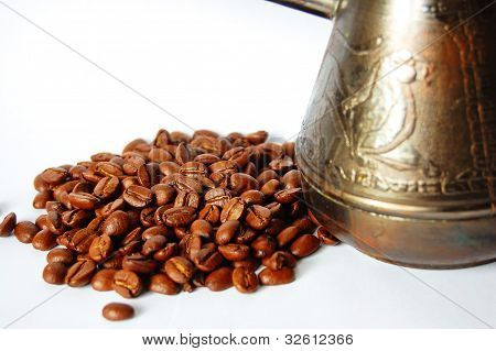 copper coffee pot with coffee beans