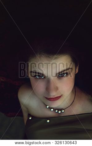 Portrait Of Young Woman On Dark Background