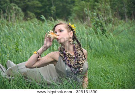 Woman In Grey Silk Dress Sitting In Tall Grass