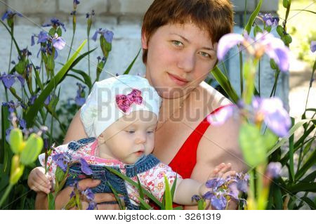 Little Girl And Her Mother Sitting In Iris Flowers