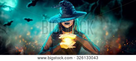 Halloween Witch girl with making witchcraft, magic in her hands, spells. Beautiful young woman in witches hat conjuring. Spooky dark magic forest background. Magician. Wide Halloween party art design