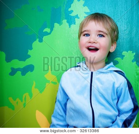 Little boy against abstract wall.