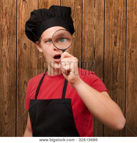 portrait of a young cook man looking through a magnifying glass against a wooden wall