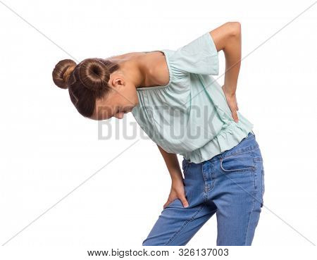 Portrait of unhappy teen girl suffering from backache, isolated on white background. Upset child massaging back suffering from discomfort ache pain. Cute young teenager hands touching back pain. poster