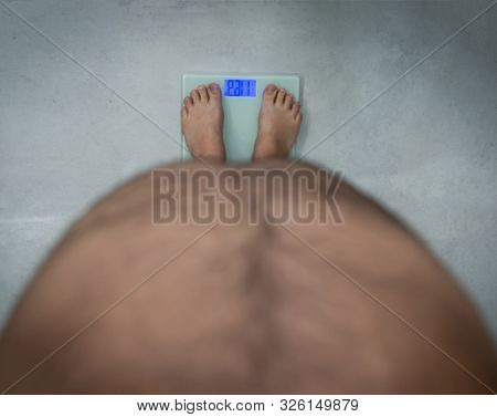 Overweight fat man with big stomach on scale personal view