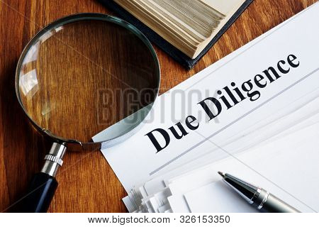 Due Diligence Concept. Stack Of Documents And Magnifying Glass.