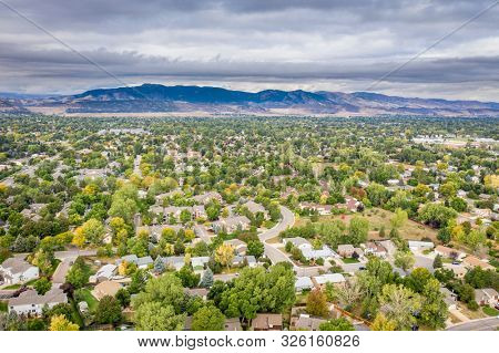 aerial view of city residential area in northern Colorado with foothills and Rocky Mountains in background, Fort Collins in early fall scenery