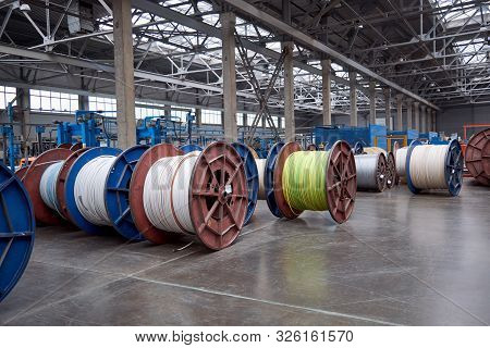 Several Rows Of Large, Heavy Metal Coils With Electrical Cables And Wires In Production. Modern Line