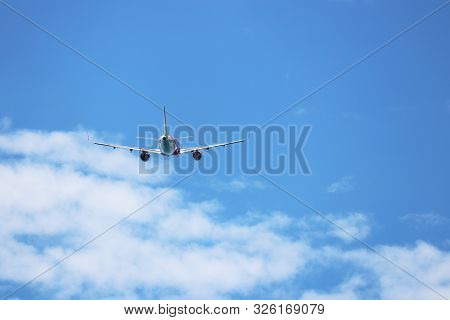 Airplane Flying In The Blue Sky On Background Of White Clouds, Rear View. Two-engine Commercial Plan