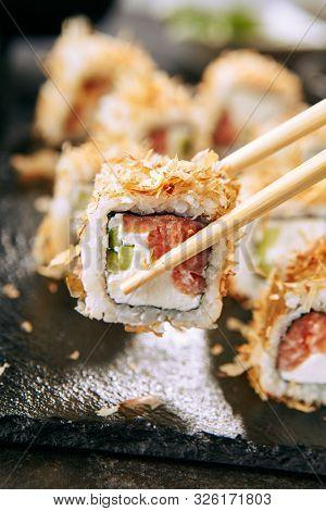 Macro shot of eating uramaki sushi rolls with cream cheese, salmon, tuna shavings or dried bonito, cucumber, nori. Taking portion of fresh katsuobushi roll in Japanese restaurant closeup poster