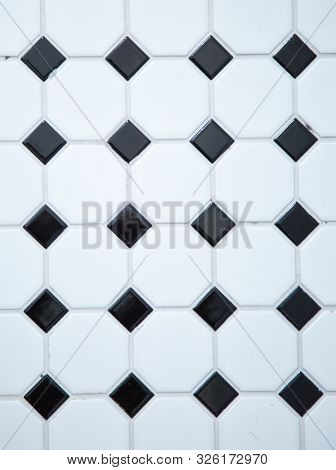 Vertical picture of a white and black  mat tiles on a wall with grey cement