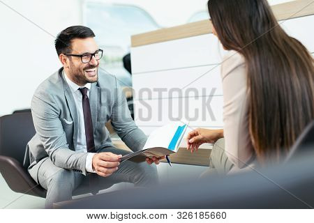 Salesperson Selling Cars At Dealership To Buyer