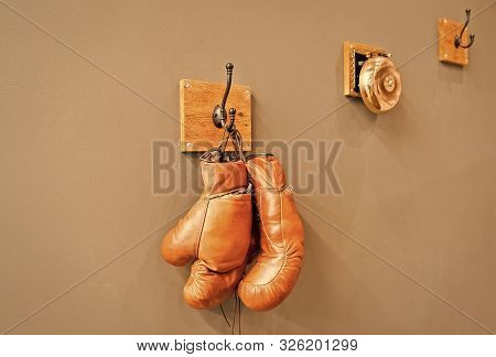 For All Your Boxing Needs. Pair Of Retro Sparring Boxing Gloves Hooked On Wall. Old Protective Sport