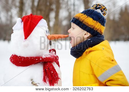 Little Boy Playing With Funny Snowman. Child Reaches For A Snowman's Carrot Nose And Wants To Bite.