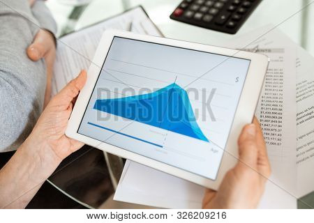 Blue financial graph on display of touchpad held by analyst or financier over workplace with papers