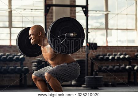 Determined african man lifting weight in gym. Muscular strong man taking efforts to lift weight barbell in fitness center. Black shirtless bodybuilder doing squatting with a barbell on shoulder.