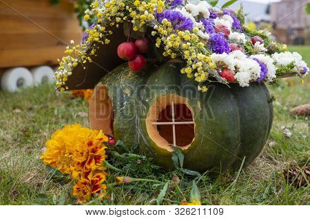 Quaint Pumpkin House With Colorful Flowers On The Roof And Marigolds At The Door Outdoors In An Urba