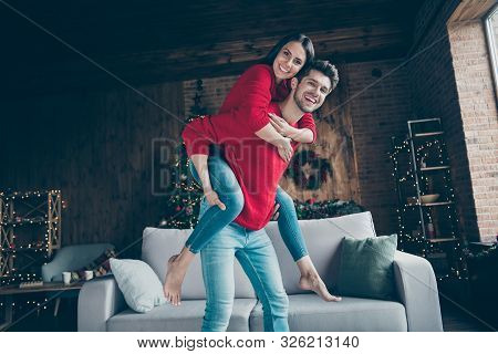 Portrait Of Romantic Couple Hug Piggyback Have Christmas X-mas Vacation Event Near Couch In House Wi